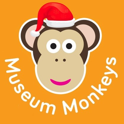 Cartoon monkey face on orange background. The monkey is wearing a Christmas hat.