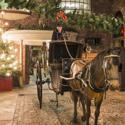 Fake horse and cart next to Christmas tree on cobbled street