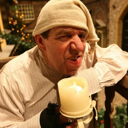 Actor dressed as Scrooge holding a candle