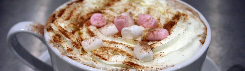A cup of hot chocolate decorated with pink and white marshmellows.