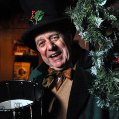 An actor dressed in Victorian clothes by a bough of holly