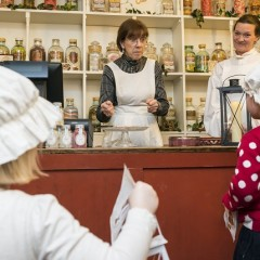 Two children and two women in Victorian dress in a sweet shop