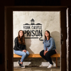 Two women sit on a bench in front of a sign that reads York Castle Prison