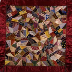 Multi-coloured patchwork quilt with a red border.
