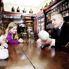 Man dressed in Victorian clothes speaks to two children in a Victorian chemist's