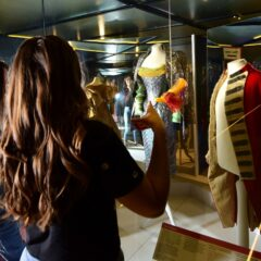 A woman points at the fashion displays. A military coat is seen on the far left and a silver dress in the centre