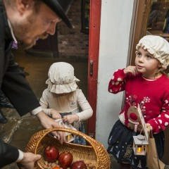 Two small girls take apples from a Victorian gentleman at York Castle Museum