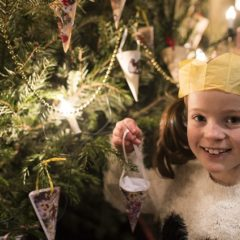 Young girl holds paper Christmas decoration in front of a Christmas tree