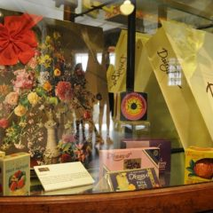 A wooden cabinet with old chocolate and sweet boxes displayed