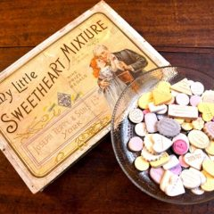An old fashioned sweet box with a glass bowl of pastel coloured lozenges