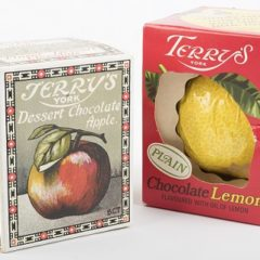 Two old chocolate boxes with a lemon and apple depicted