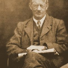 Photo of middle-aged man seated wearing suit and glasses