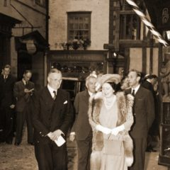 Four suited men and woman wearing dress, hat and fur walking down a recreated Victorian street in a museum