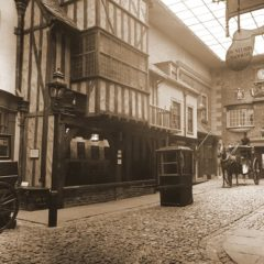 Sepia photo of recreated Victorian street with shop fronts and horse and cart