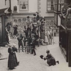 Men and women in Victorian costume on a recreated street