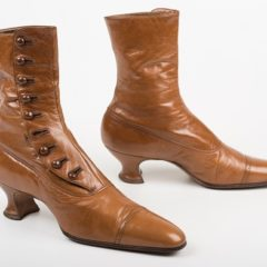 A pair of brown leather boots. The boots have a heel and buttons running up and down them.