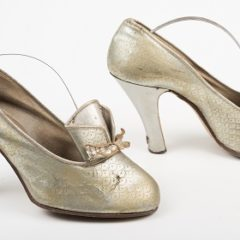 A pair of heeled, metallic shoes. The shoes have a decorative ribbon on the front.