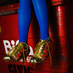 A person wearing electric blue tights and gold laced trainers, sat on a red bin.
