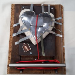 A metal heart taped down to an object. The object has several layers.