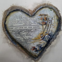 A fabric heart decorated with pictures and words.
