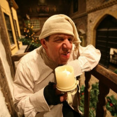 A man wearing a nightcap and nightshirt holding an electric candle.