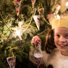 A girl wearing a Christmas cracker hat holding a Christmas tree decoration.