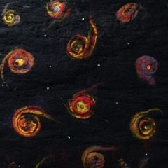 A knitted piece of art resembling spiral galaxies in the night sky.