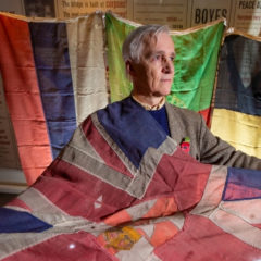 A man holding an historic flag and stood in front of three other historic flags.