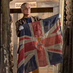 A man stood in a replica trench holding a flag resembling the Union Jack.