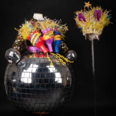 A colourful sequin dress with three giant party poppers stuck to it, and a piece of headgear made of various coloured ribbons and stars.