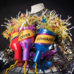 A colourful sequin dress with three giant party poppers stuck to it, one which says 'congrats'.