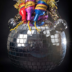 A glitterball dress with three giant party poppers stuck to it, one which says 'congrats'.