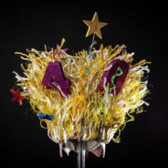 A piece of headgear made of various coloured ribbons and stars, with the numbers 4 and 0 poking out of it.