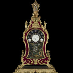 18th century clock, decorated in gold and red velvet. Below the clock face is a depiction of a waterfall scene. The clock is topped with four dancing figures below a temple and a figure of Hercules.