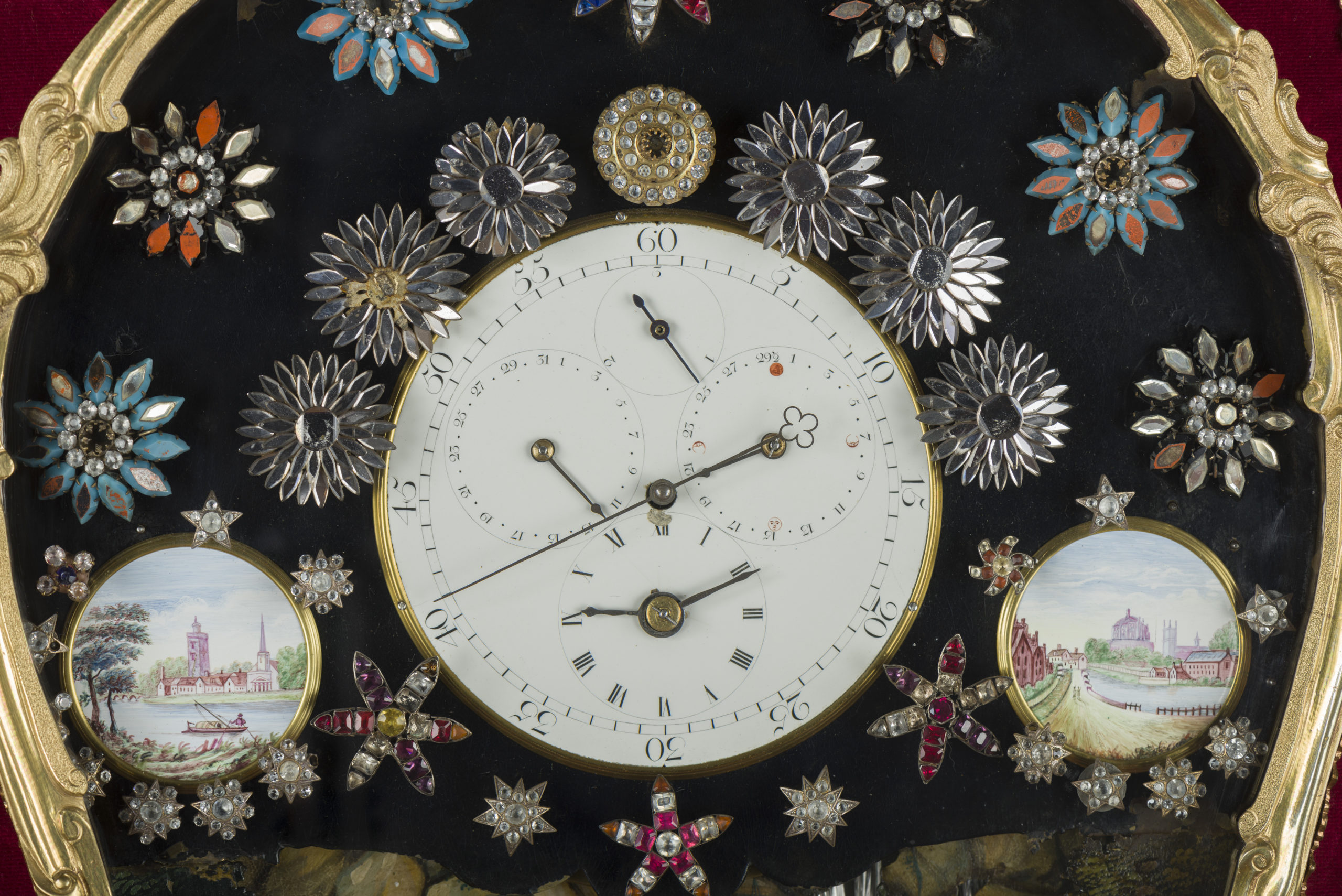 Close up on clock face, showing jewelled flowers/stars which surround the clock face. On either side of the clock face, there are small pictures of river-side scenes.