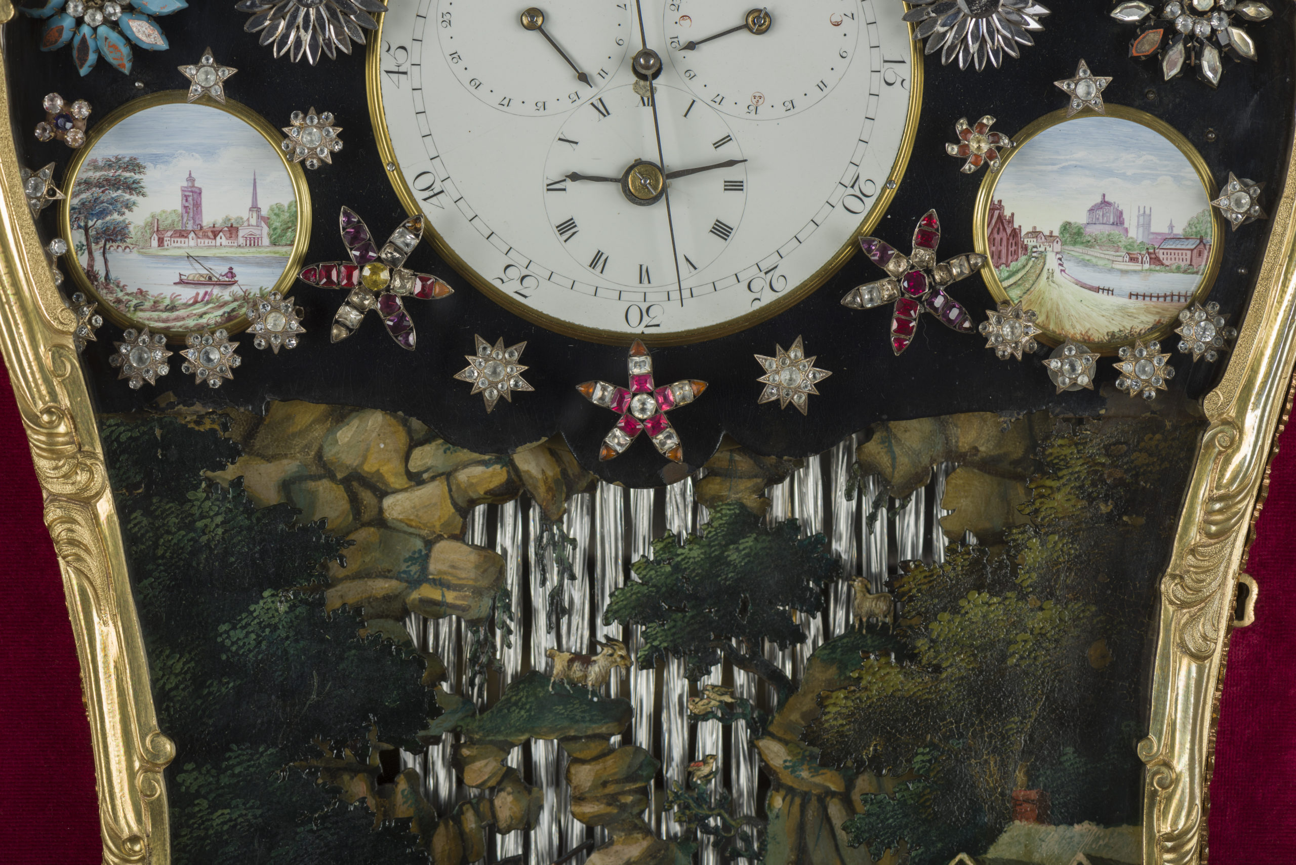 Close up on clock face, showing jewelled flowers/stars which surround the clock face. On either side of the clock face, there are small pictures of river-side scenes. Below this, there is the top of a waterfall scene, showing a goat and several birds in the greenery surrounding this scene.