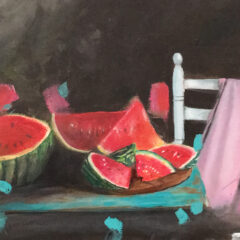Watermelons are cut up on a blue table. A white chair has a pink scarf thrown over it.